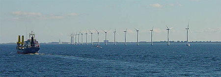Ship laden with containers passes wind turbines at sea