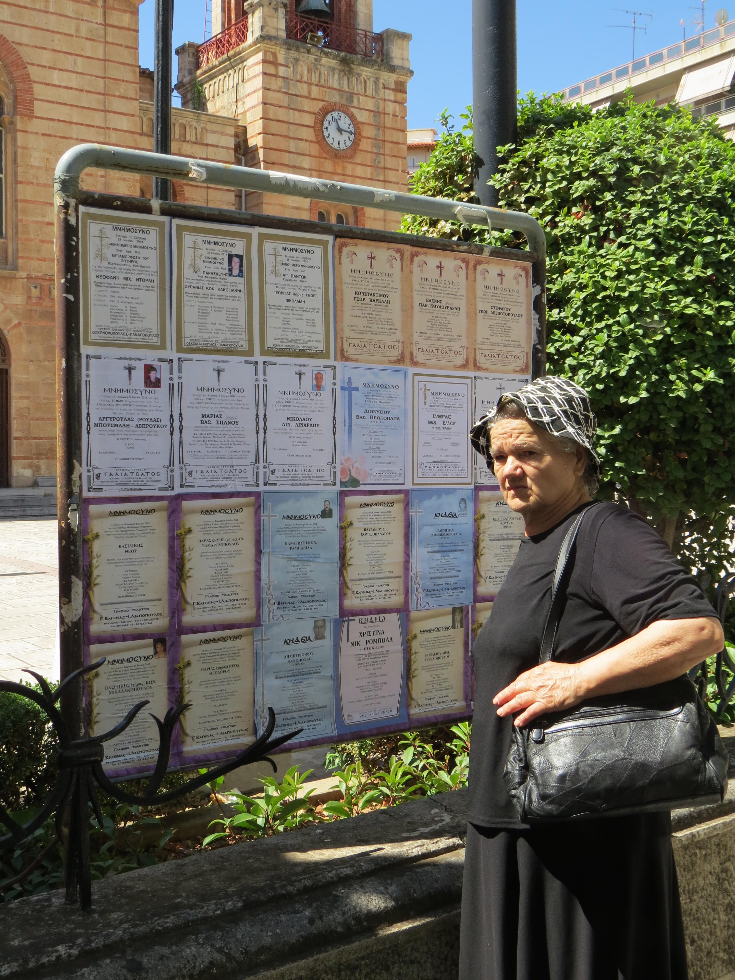 Greek widow checks church obituary board