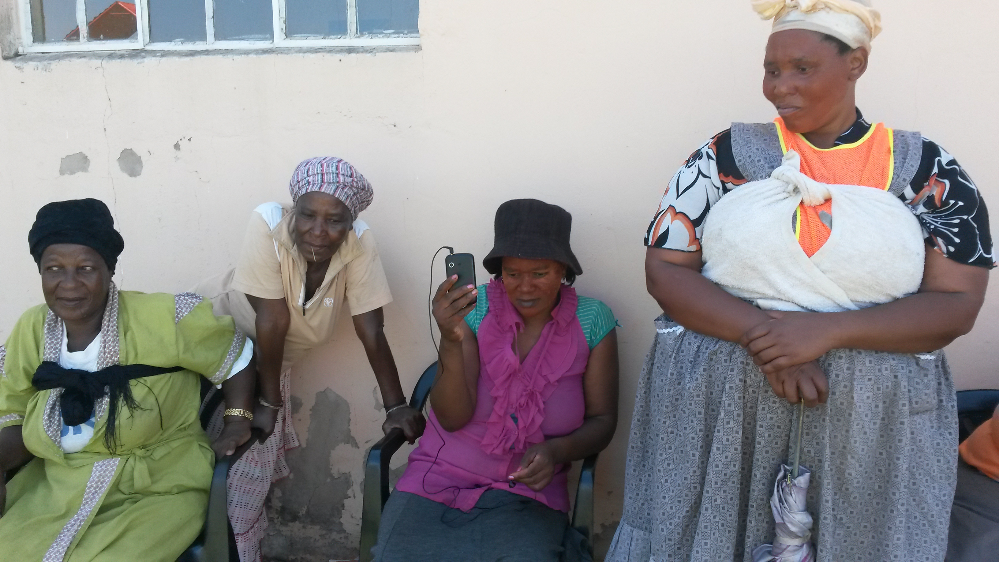 rural women in KwaZulu Natal, South Africa listening to radio on cellphone