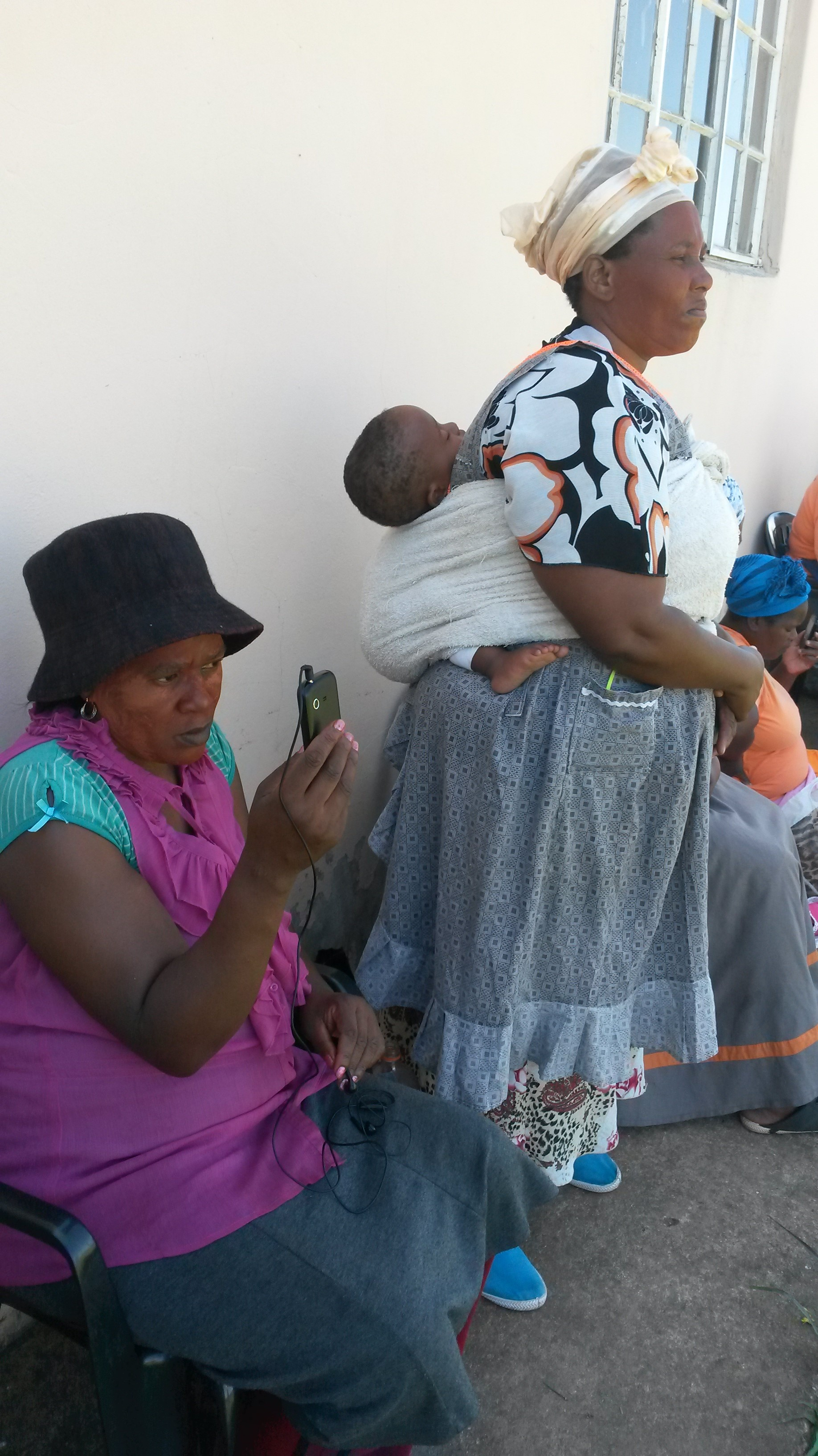 rural African woman with baby on back listening to radio on mobile phone