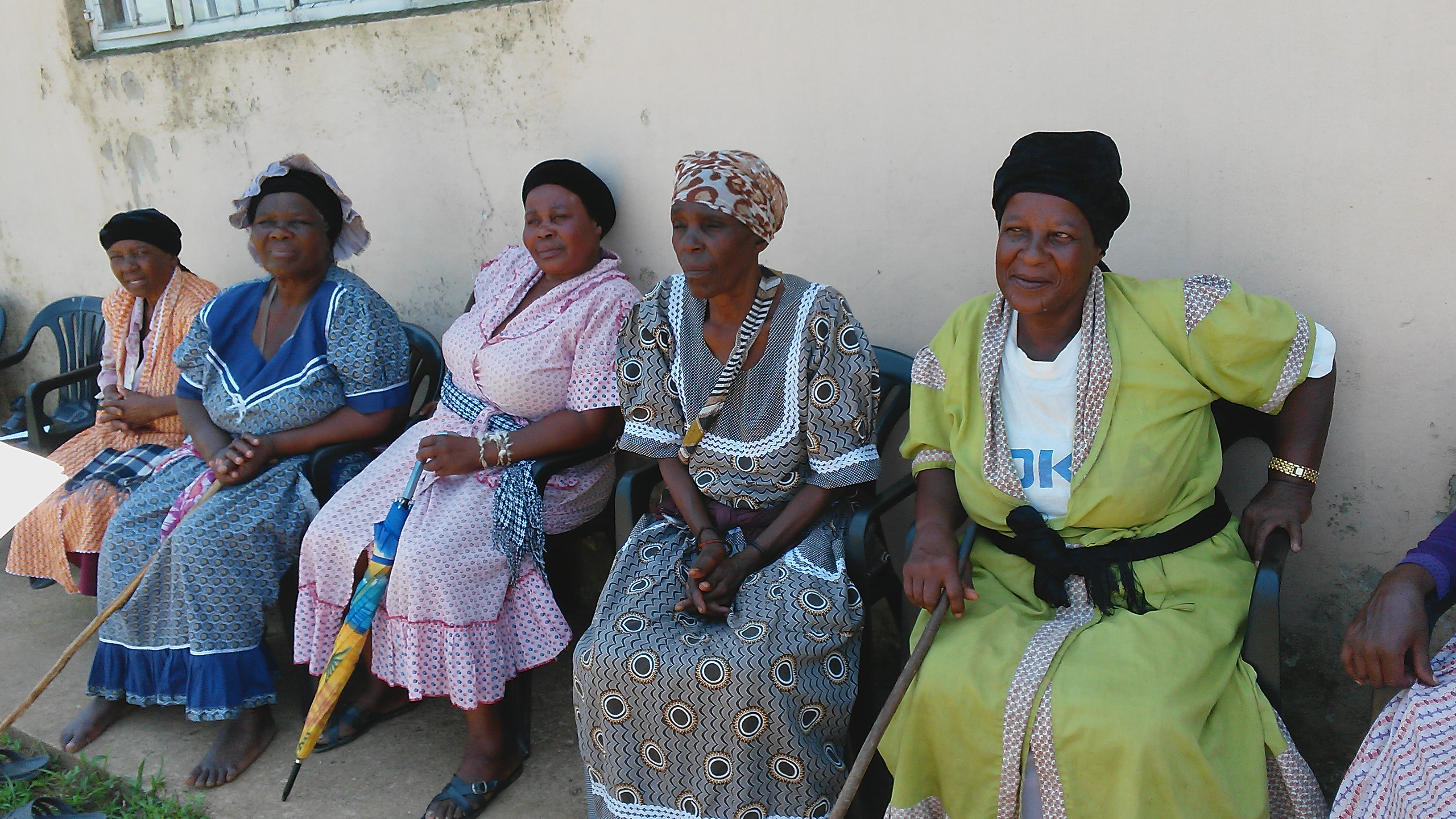 Older women sitting at rural community centre with walking sticks and umbrellas