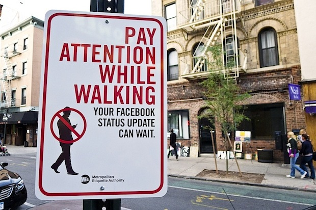 Street sign warning pedestrians to pay attention while walking