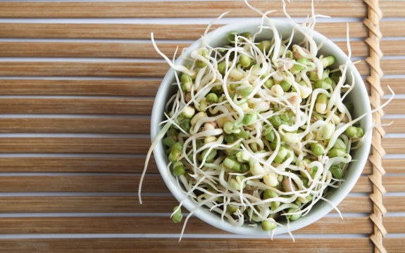 mung bean sprouts in bowl on bamboo